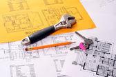 Outils sur les plans de la maison y compris le crayon, une clé et clé de singe. — Photo