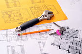 Tools on house plans including pencil, keys and monkey wrench. — Foto de Stock
