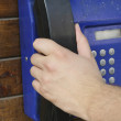 Royalty-Free Stock Photo: Hand picking up public phone horn