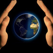Royalty-Free Stock Photo: Hands under blue planet isolated on black background