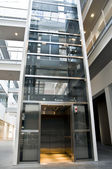 Big elevator made of glass and steel inside a business building — Stock Photo