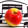 Stock Photo: Music notation elements and apple