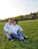 Young couple sitting on the grass in the countryside — Stock Photo