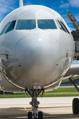 Closeup of airplane nose with pilot cabin against blue sky — Stock Photo