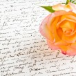 Stock Photo: Red yellow rose over hand written love letter