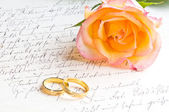 Rose, rings over handwritten letter — Stock Photo