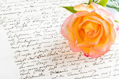 Red yellow rose over a hand written love letter — Stock Photo