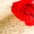 Stock Photo: Red rose over hand written letter
