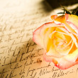 Stock Photo: Red yellow rose over a hand written letter