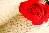 Red rose over a hand written letter — Stock Photo