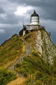 Nugget Point Light House and dark clouds in the sky — Stock Photo