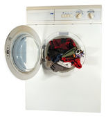 The washing machine with the open hatch inside color linen — Stock Photo