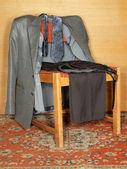 Kleider hängen an einem alten stuhl — Stockfoto