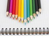 Mångfärgade pennor på spiral notebook — Stockfoto