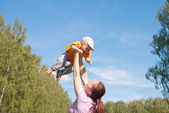 Mother playing with baby in the sky — Stock Photo