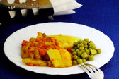 Fish with carrot, green peas and spices on the white plate — Stock Photo