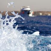 Éclaboussure de l'eau avec yacht de mer à l'arrière-plan — Photo