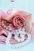 White pearls in a pink bag with a rose — Stock Photo