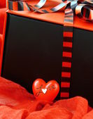 Red box with a gift and a red heart — Stock Photo