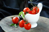 Cherry tomatoes and basil in a white gravy boat — Stock Photo
