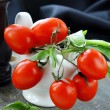 Cherry tomatoes and basil in a white gravy boat - Stock Photo