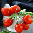 Cherry tomatoes and basil in a white gravy boat - Foto Stock