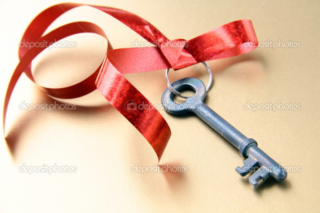 Old key with a red ribbon  on  gold  background — Stock Photo #4754271