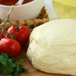 Dough, tomato sauce, olive oil and tomato - Stock Photo