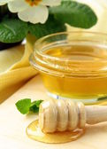 Fresh golden honey in jar with a wooden spoon — Stock Photo