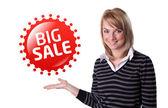 Jonge gelukkig zakenvrouw presenteren van grote verkoop teken op haar hand — Stockfoto