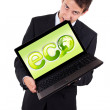 A businessman bites a laptop with eco sign — Stock Photo #5252218