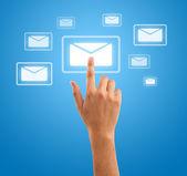 Hand pressing futuristic mail symbol on blue background — Stock Photo