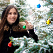 Pretty woman is standing beside a fir tree, smiles happy and holds a glass — Stock Photo