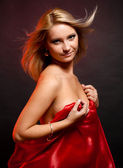 Beautiful blonde in the studio on a black background with red cloth — Stock Photo