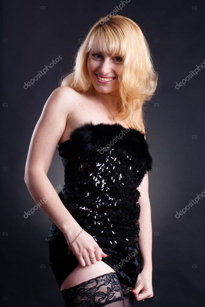 Beautiful blond model in black dress posing on black background  — Stock Photo #4497885
