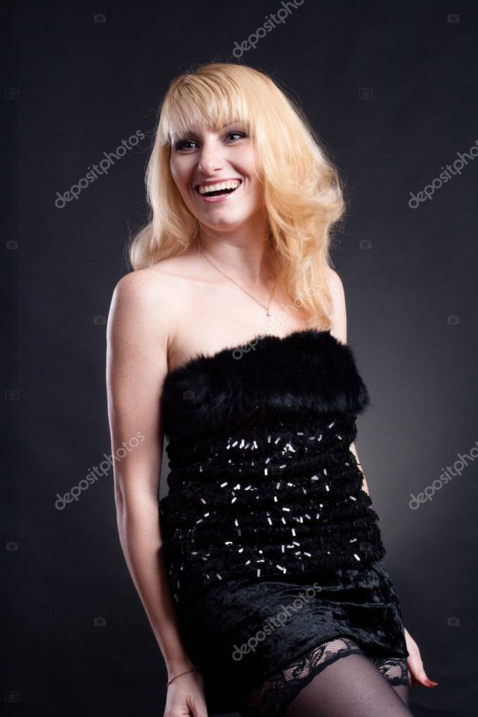 Beautiful blond model in black dress posing on black background  — Stock Photo #4497886
