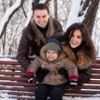 Attractive family having fun in a winter park — Stock Photo