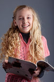 Studio portrait of a blonde girl with a magazine — Stock Photo