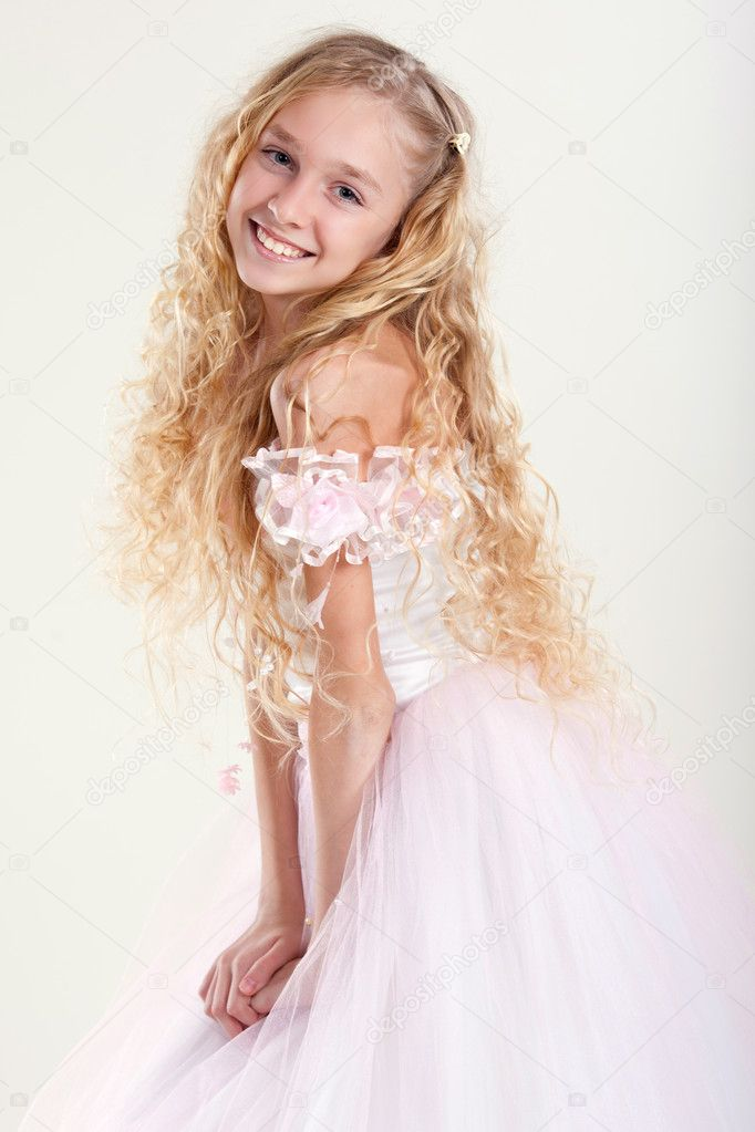 Beautiful little girl in  dress with long hair on grey background — Stock Photo #5356711