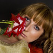 Stock Photo: Beautiful girl with red flower looks at you, focusing on eyes