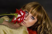 The beautiful girl with a red flower looks at you, focusing on eyes — Stock Photo