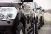 группа автомобилей стоят в одном количество темного цвета — Стоковое фото