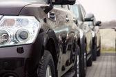 Grupo de coches están parados en un número de color oscuro — Foto de Stock