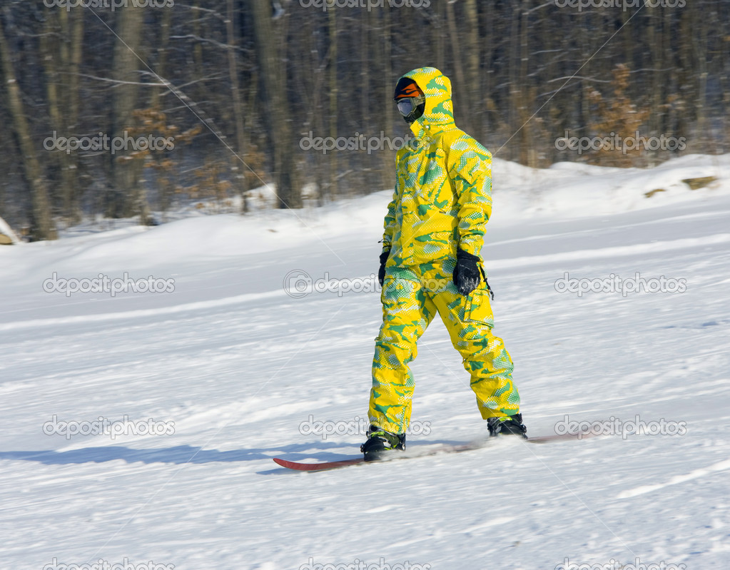 Snowboarder in a yellow suit going from mountain on against wood — Stock Photo #4559753