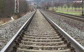 Railways on a stone platform, rails, road — Stock Photo