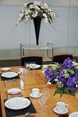 Restaurant table setup with cut flowers — Stock Photo