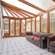 Conservatory extension of a family home with leather sofa and tiled floor — Stock Photo #5202463
