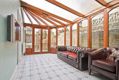Conservatory extension of a family home with leather sofa and tiled floor — Stock Photo
