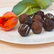 Royalty-Free Stock Photo: Chocolates and tulip on a white plate