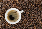 Background from coffee grains and a cup from coffee, the top vie — Stock Photo